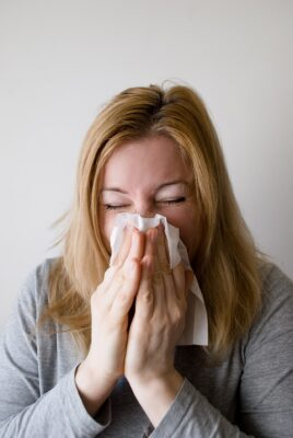 woman sneezing because of office allergens