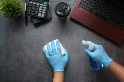 person cleaning desk as part of Houston office cleaning services for hot desking and coworking spaces